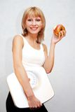 Healthy lifestyle. Beautiful young woman holding measuring instrument and eating an apple Stock Images