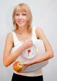 Healthy lifestyle. Beautiful young woman holding measuring instrument and eating an apple Royalty Free Stock Image