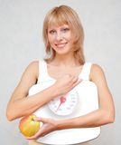 Healthy lifestyle. Beautiful young woman holding measuring instrument and eating an apple Stock Photos
