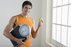 Healthy lifestyle. Sportsman holding scale and apple. Concept: healthy lifestyle Stock Photography