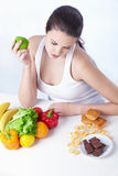 Healthy lifestyle. Beautiful girl choose between healthy food and sweet on a white background royalty free stock image