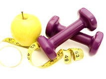 Healthy lifestyle. Apple and weights with measuring tape on a white background Royalty Free Stock Photography
