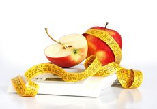 Healthy lifestyle. Close up of two apples and a tape on a balance. Concept of healthy lifestyle Royalty Free Stock Photography