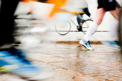Healthy lifestyle. Intentionally motion blurred abstract image of runners and a person cycling. Low angle view Royalty Free Stock Photos
