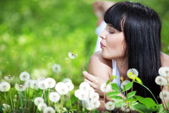 Healthy lifestyle. Young beautiful woman resting on fresh green grass Royalty Free Stock Image