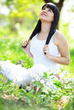 Healthy lifestyle. Young beautiful woman resting on fresh green grass Royalty Free Stock Photography