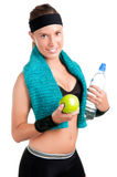 Healthy Lifestyle. Woman holding an apple and a bottle of water after a workout in the gym, isolated in a white background Royalty Free Stock Images