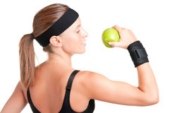 Healthy Lifestyle. Woman about to eat a green apple after her workout at the gym Royalty Free Stock Photography