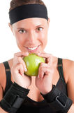 Healthy Lifestyle. Woman about to eat a green apple after her workout at the gym Stock Photography