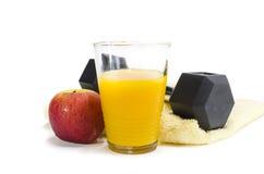 Healthy Lifestyle. Black gym dumbbell,yellow towel and orange juice, isolated on white background Stock Image