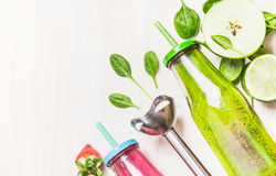Healthy lifestyle background with green smoothie drink in bottle, blender and ingredients on white wooden Royalty Free Stock Image