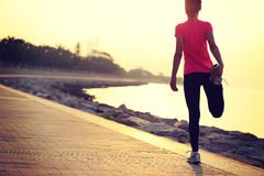 Healthy lifestyle beautiful asian woman stretching legs before running. At sunrise seaside Royalty Free Stock Image