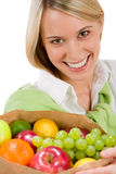 Healthy lifestyle - cheerful woman with fruit Stock Image