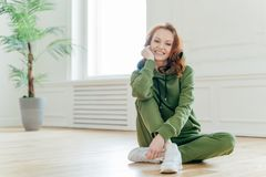 Healthy lifestyle concept. Beautiful slim young woman with red wavy hair, keeps hand under chin, smiles happily, dressed in stock images