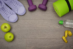 Healthy lifestyle concept. Fitness equipment: sneakers, water,apple and mat for fitness classes on  floor Royalty Free Stock Photos