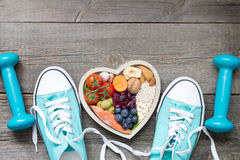 Healthy lifestyle concept with food in heart and sports fitness accessories. On wooden board