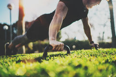 Healthy lifestyle concept.Functional training outdoors.Handsome sport athlete man doing pushups in the park on the sunny. Morning. Blurred background.Horizontal Royalty Free Stock Image