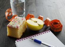 Healthy lifestyle concept - glass of water, apple, cake and notebook. On the dark wooden background, weight loss concept royalty free stock photos