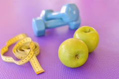 Healthy lifestyle concept - green apple with dumbbells and yellow measuring tape Stock Photography
