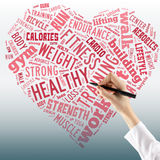 Healthy lifestyle concept - heart in word collage. Close up of f. Emale hand with black pen Royalty Free Stock Image