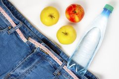 Healthy lifestyle concept. Jeans with a measuring tape instead of a belt, apples and a bottle of water.  stock images