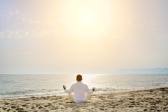 Healthy lifestyle concept - man doing yoga meditation exercises on the beach. Man doing yoga meditation exercises on the beach at sunset- healthy lifestyle Royalty Free Stock Photography