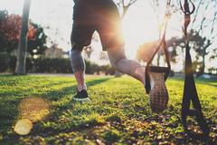 Healthy lifestyle concept.Muscular athlete exercising trx outside in sunny park.Great TRX workout.Young handsome man in. Sportswear doing exercising outdoors stock images