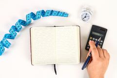 Healthy lifestyle concept with notepad. Weight loss or diet concept. Calculator, clock, measure tape on a white table background with copy space for design royalty free stock photography