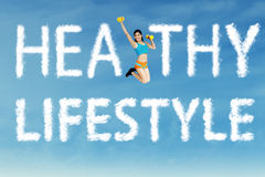 Healthy lifestyle concept. A sports woman jumping with clouds shaped of healthy lifestyle Royalty Free Stock Photos