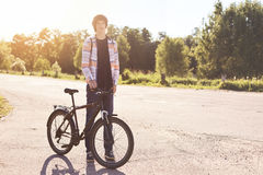 Healthy lifestyle concept. Teenage male with trendy hairstyle wearing casual shirt, jeans and sport shoes standing with bicycle on. Road having rest outdoors Royalty Free Stock Photo