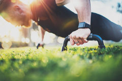 Healthy lifestyle concept.Training outdoors.Handsome sport man doing pushups in the park on the sunny morning. Blurred. Background royalty free stock photo