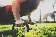 Healthy lifestyle concept.Training outdoors.Handsome sport man doing pushups in the park on the sunny morning. Blurred Royalty Free Stock Photos