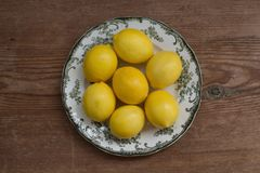 Healthy lifestyle concept. Lemons on a white plate over rustic table stock photography