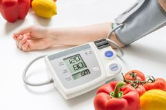 Healthy lifestyle concept. Woman is measuring blood pressure with monitor. Vegetables in background Royalty Free Stock Photography