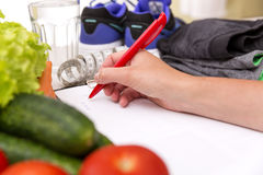 Healthy lifestyle concept. Writing weight loss plan with fresh vegetable diet and fitness.  royalty free stock photo