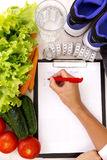 Healthy lifestyle concept. Writing weight loss plan with fresh vegetable diet and fitness royalty free stock photography
