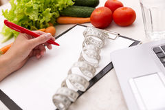 Healthy lifestyle concept. Writing weight loss plan with fresh vegetable diet and fitness. Sports stock photography