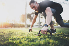 Healthy lifestyle concept.Young athlete exercising push up outside in sunny park. Fit shirtless male fitness model in Stock Images