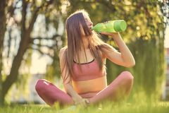Healthy lifestyle concept. Young fitness girl in sportswear in lotus pose sitting on green grass and drink water. Healthy lifestyle concept. Young girl in Royalty Free Stock Photos