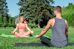 Healthy Lifestyle. Couple practicing yoga outdoors sitting in lotus pose on yoga mats doing meditation woman looking royalty free stock image