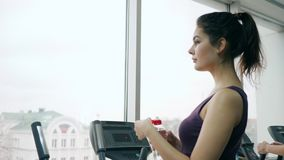 Healthy lifestyle, cute girl drinks cool water from plastic bottle during exercise fitness studio stock video footage