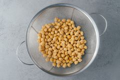 Healthy lifestyle and dieting concept. Top view of garbanzo or chickpeas in sieve. Organic product. Making vegetarian salad. Uncooked food royalty free stock images