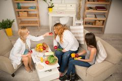 Healthy lifestyle explanation. Young dietitian treating patient with healthy fruit and vegetables royalty free stock photography