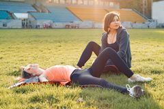 Healthy lifestyle, healthy family. Smiling fitness mother and teen daughter together resting at stadium after running on sunny. Spring evening stock images