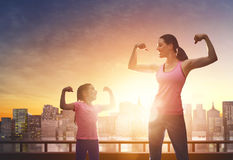 Healthy lifestyle. Family sport. Athletic young women and her daughter are running on background of urban landscape. Healthy lifestyle. Family sport Royalty Free Stock Photography