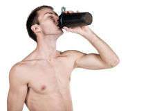 Healthy lifestyle and fitness. Handsome guy sports a physique, with a naked body, drinks water from a bottle, isolated on a white Royalty Free Stock Photos