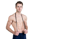 Healthy lifestyle and fitness. Handsome guy sports a physique, with a naked body, with a skipping rope in his hands, isolated on a royalty free stock photography