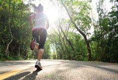 Healthy lifestyle fitness sports woman running. At forst road Royalty Free Stock Image