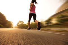 Healthy lifestyle fitness sports woman running leg. Healthy lifestyle fitness sports woman legs running at sunrise road Stock Photography