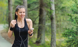 Healthy lifestyle fitness sporty woman with headphone jogging in stock photography